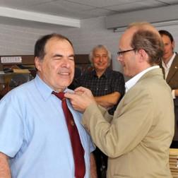 Serge Etienne, serrurier d'art, se fait remettre sa rosette par Cyril Kretzschmar.